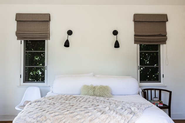 Bedroom with white bedding, brown window shades and black wall lamps