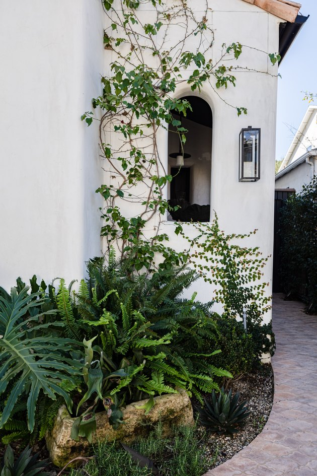 White mediterranean home with terra-cotta roofing and green ivy