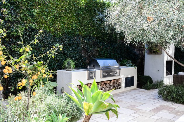 A grill with firewood surrounded by plants and trees on a patio