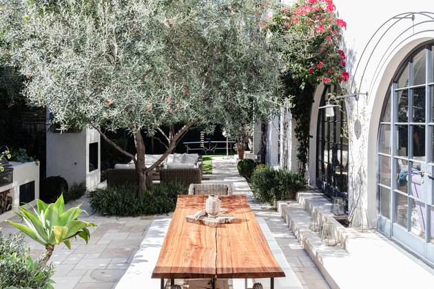 Wood patio table with plants and a white Mediterranean style building with arch windows