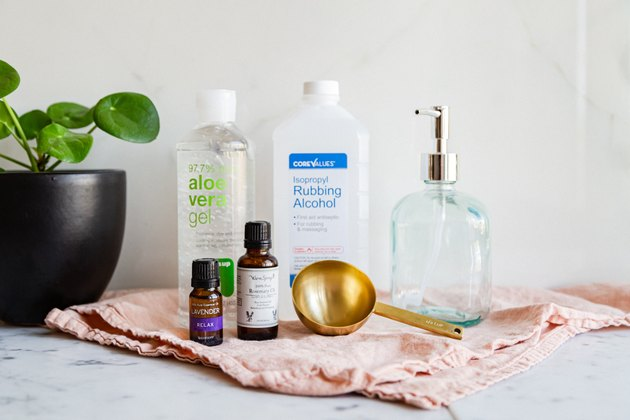 rubbing alcohol, aloe vera gel, essential oil, a measuring cup, and a glass jar with a pump full of diy hand sanitizer