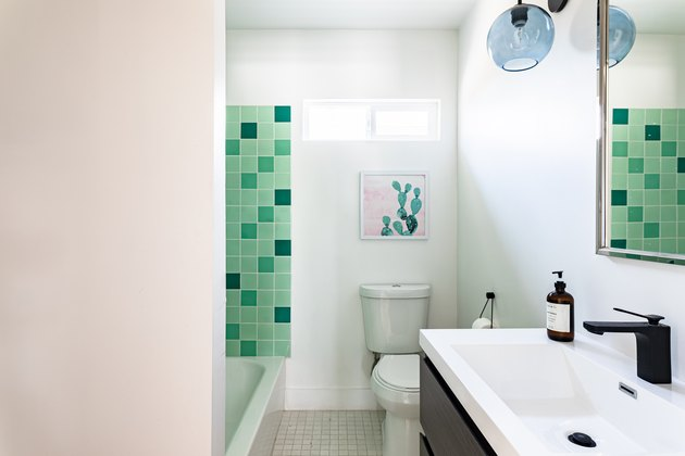 white toilet, green square shower tile, wood vanity with white ceramic wink, blue light fixture, white walls, tan tile floor