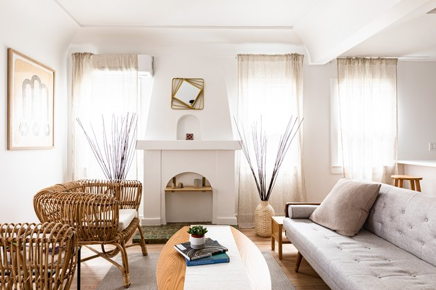 living room with white couch and woven chairs