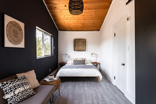 Bold bedroom with gray wood floor, wood ceiling, black-white walls and wicker accents