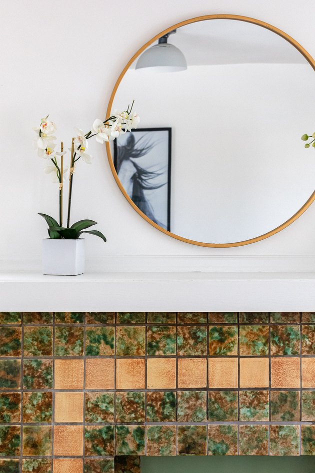 A decorative fireplace with colorful tiles, and large round mirror and white orchids