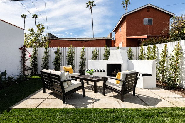 Paver patio with an outdoor fireplace, patio chairs and table surrounded by a white face lined with green trees