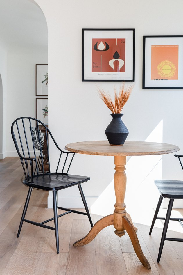 dining table with two chairs and two framed artworks on the wall