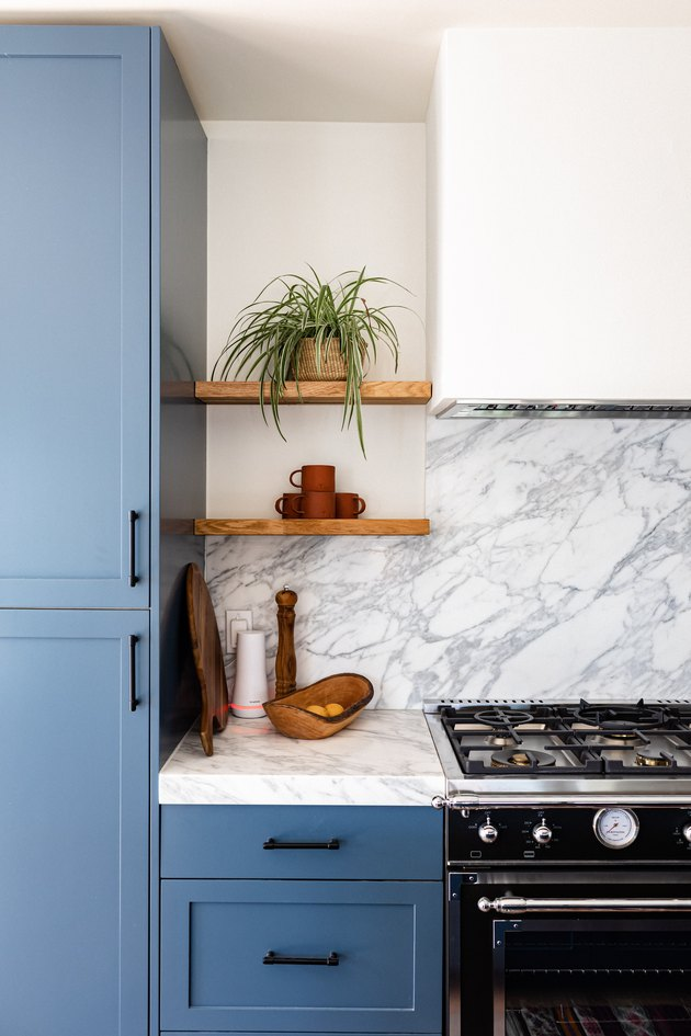 blue and white kitchen with stove hood vent and marble backsplash