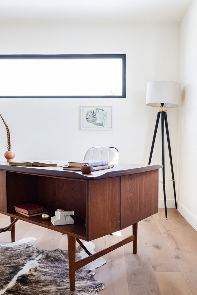 A wood desk on wood floor with a fur rug and a black-white floor lamp with Home Office Desk Ideas