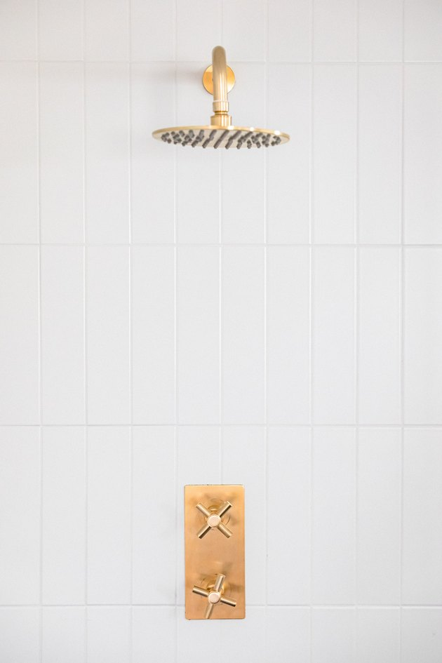 Gold shower head and white tile wall