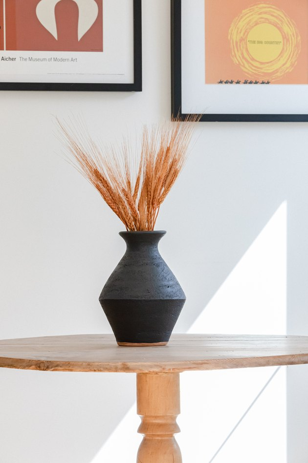 A black vase with dried wheat on a wood table and colorful wall art