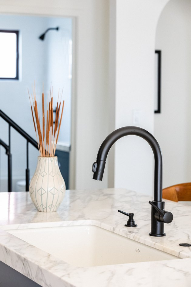 White kitchen sink countertop with a black faucet and a white vase with dried plants