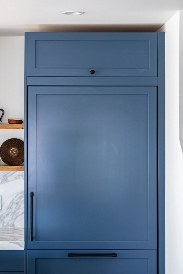 Blue kitchen cabinets with black handles