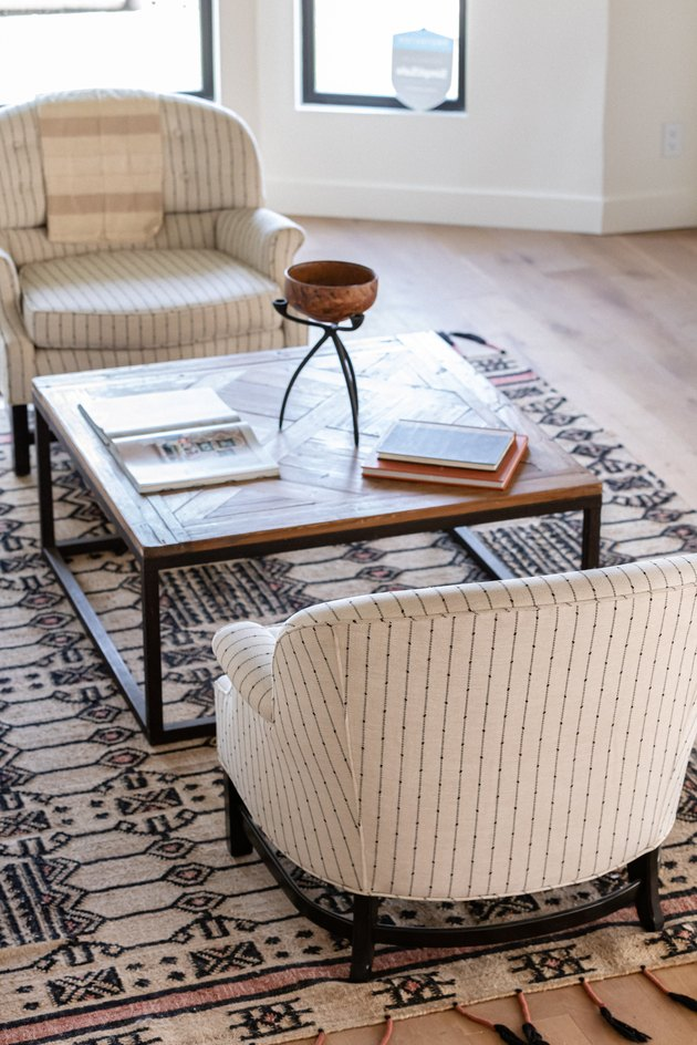 Beige living room chairs with a wood coffee table, beige-black rug and wood floors