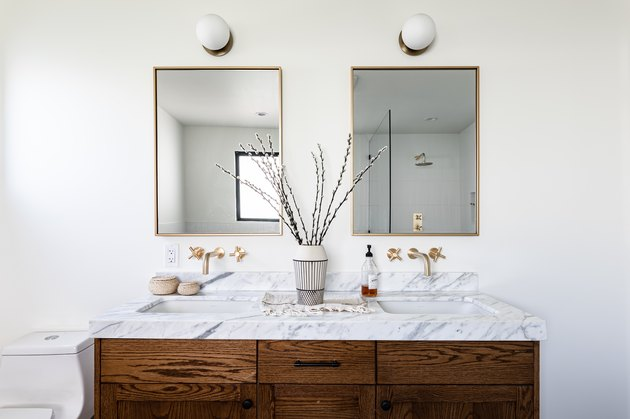 wood bathroom vanity with marble vanity top, a black and white vase with flowers, two mirrors over double sinks with white, round sconces overhead