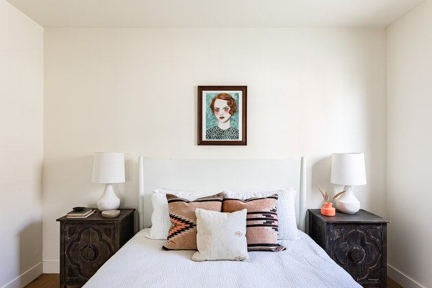 white bedroom with dark wood side tables and painting over bed