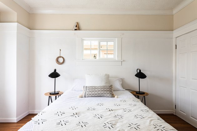 Boho bedroom with black table lamps, white walls and wood floors