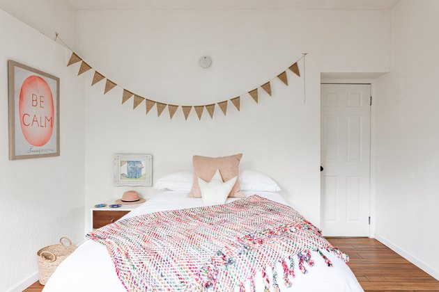 A white and pink palette from color wheel accented bedroom with white walls and wood floors