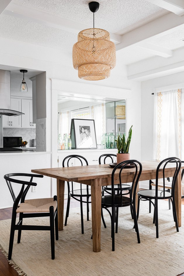 Wood dining table with black chairs on a neutral fiber rug and a wicker pendant light