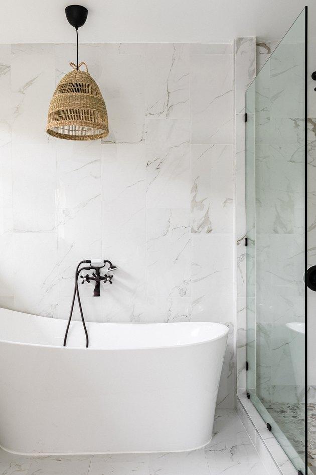 A minimalist bathroom with a bathtub, glass door shower and wicker light fixture