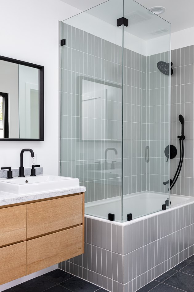 Modern bathroom with glass-walled shower over white-tiled bathtub, black faucets and shower head, white sink, and black-framed mirror