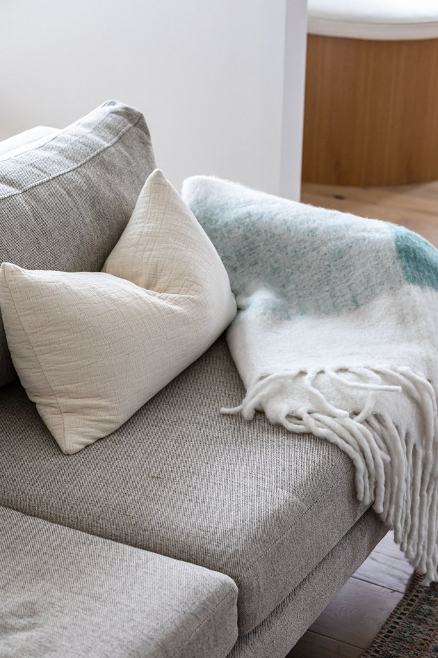 Grey couch with white pillow and teal blanket against hardwood floor and white walls