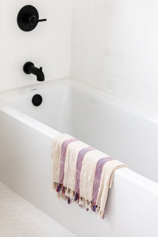 White bathtub with black faucet and handle with white and purple towel hanging on the tub in white room