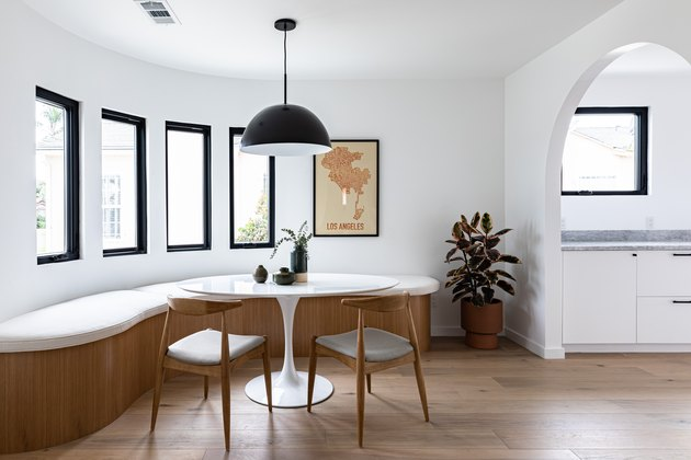 small spaces Contemporary curved dining room with curved bench, small round table, chairs, pendant lamp, and tall windows with view of hallway via archway