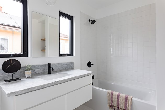 White tiled bathroom with bathtub, black shower head and faucet, black-framed windows, and marble countertop
