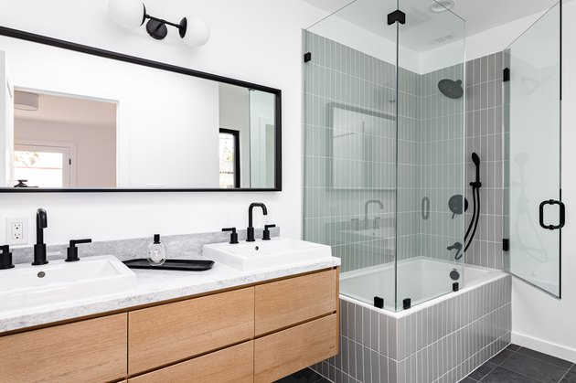 Modern bathroom with glass-walled shower over white-tiled bathtub, black faucets and shower head, white sinks, and black-framed mirror