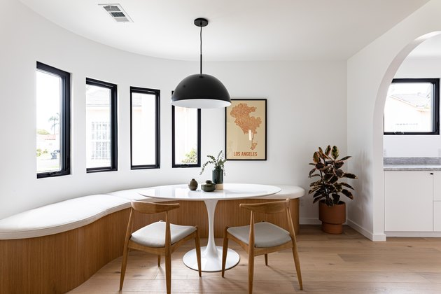 Contemporary curved dining room with curved bench, small round table, chairs, pendant lamp, framed print, and tall windows with view of hallway via arch