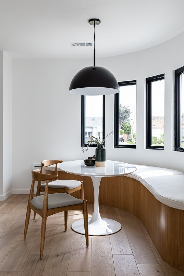 eco-friendly home design with contemporary curved dining room with curved bench, small round table, chairs, pendant lamp, and tall windows