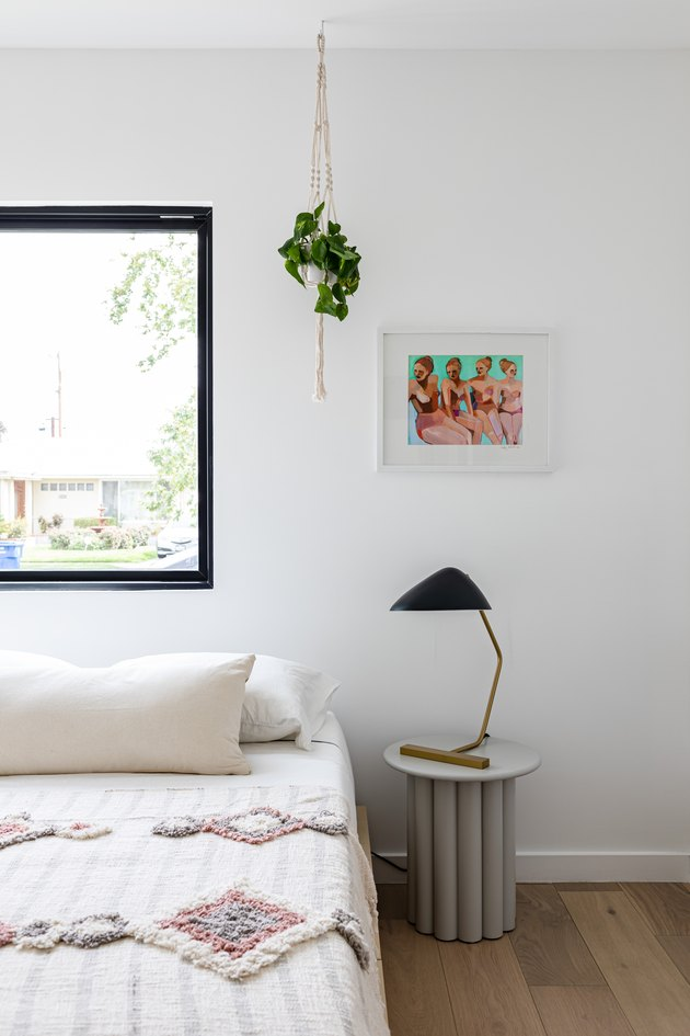 Bedroom with side table with lamp, white bed with pillow and quilted blanket, hardwood floor, white wall with window, hanging plant, and painting