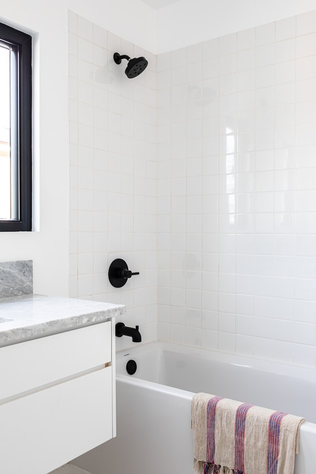 Modern bathroom with white bathtub with black faucet, white and purple towel hanging on the tub, and marble countertop