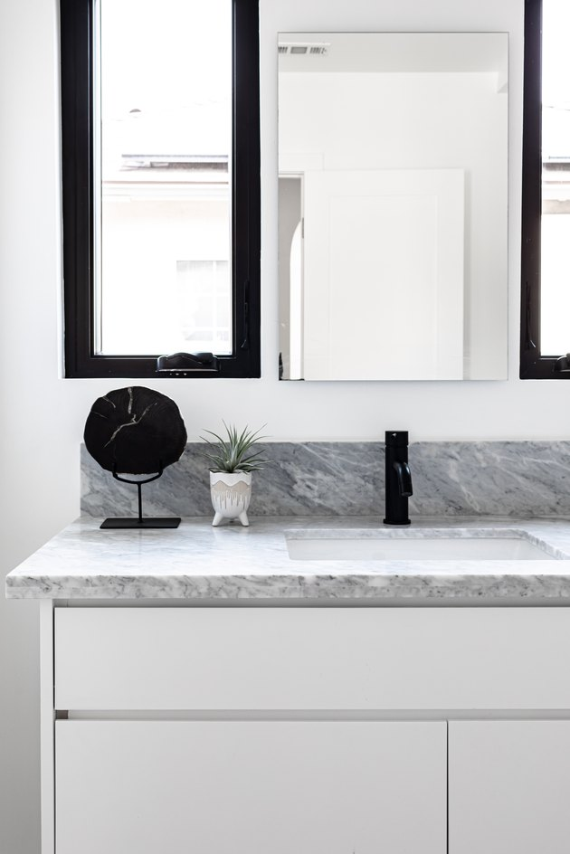 White cabinets and marble countertop for sink in bathroom with mirror and small plant, with mirror and small cabinet on white wall