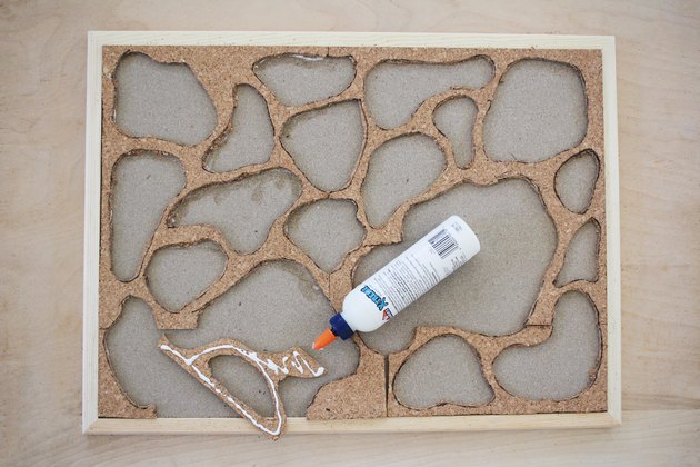 gluing pieces of cork to a bulletin board frame