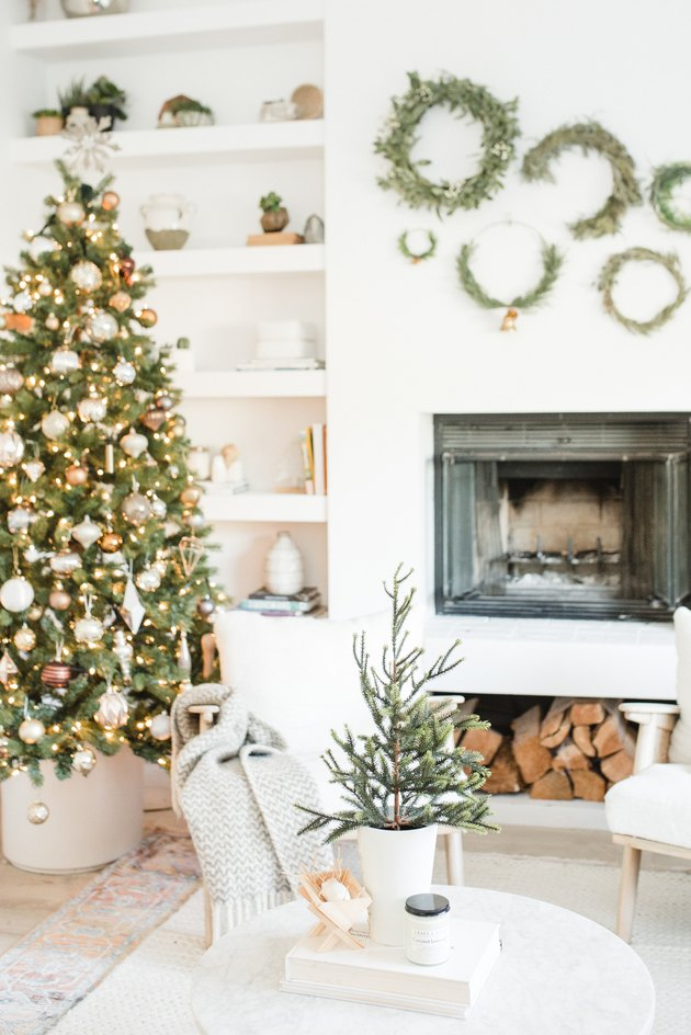 white and gold Christmas colors in living room fireplace with Christmas tree and boho decor