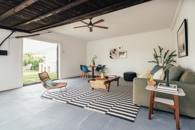 Small Garage Ideas in a Living room in a California-bohemian style: cement floor, wood ceiling, ceiling fan, black and white rug, rattan accent chair, plant, coffee table and couch.A renovated garage with living area, cement floor, and wood ceiling.
