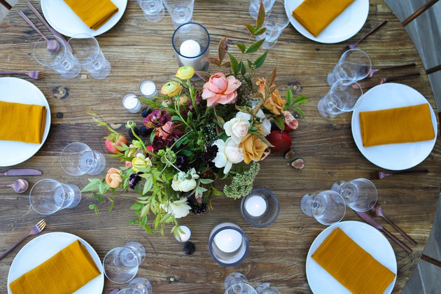 a rustic round wooden table with a large floral centerpiece and a gold napkin in the center of each plate