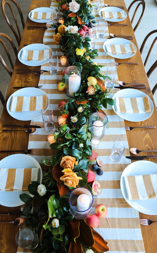 A long thanksgiving table with a white and gold striped runner and matching napkins on each plate