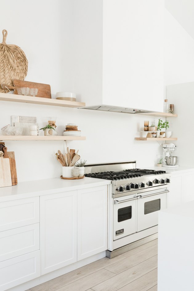 Large white kitchen with boho decor and professional range with double oven stove