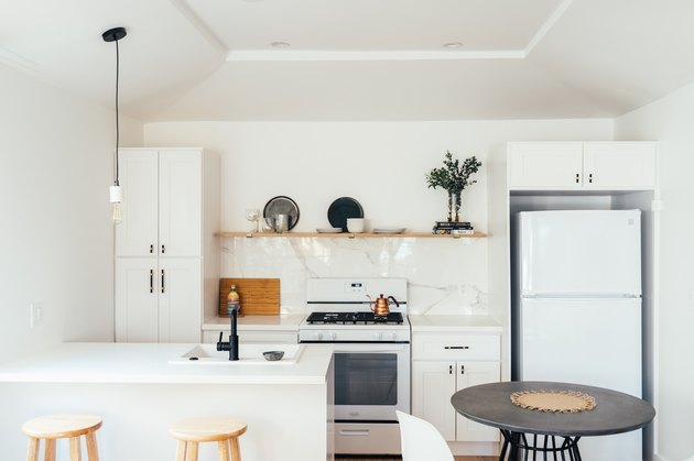 Small kitchen with white cabinets and marble backsplash. Wood open shelving, and one hanging pendant light.