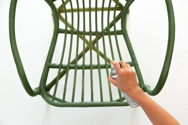 Hand with green spray paint can and rattan chair