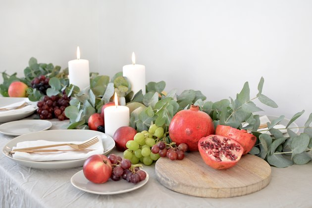 a table runner made of bunches of eucalyptus garnished with pomegranates and grapes