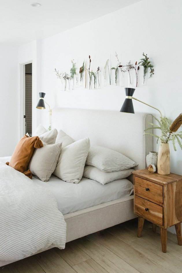 beige upholstered headboard with white bedding and plat hangings on wall