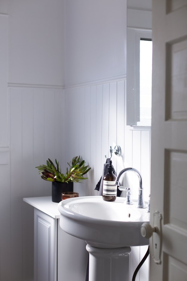 walls, wainscotting, sink, and vanity are all white in this bathroom