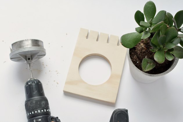a hole saw and a potted plant next to a square of plywood that has had a large circle cut out of it