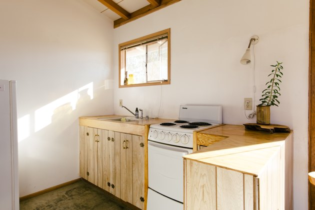 a kitchen with natural wood cabinets and an small electric stove