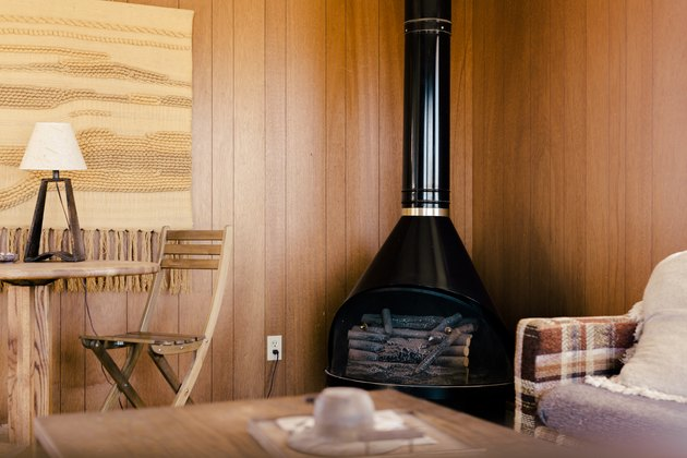 rustic decor with a wood-burning stove in the corner of a room with retro wood paneling