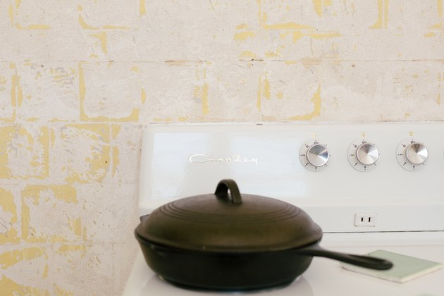 a cast-iron pan with a lid on th burner of a vintage crossly stove
